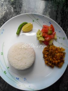 spring onion- split bengal gram stir fry, tomato- cucumber salad, green chili, piece of lime served with flaky rice